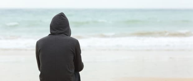 man with addiction looking out to ocean