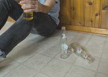 Man sitting on floor holding alcohol bottle with other empty bottles