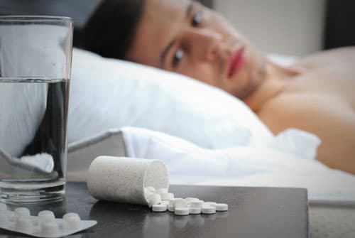 Man looking at Zolpidem pills on nightstand