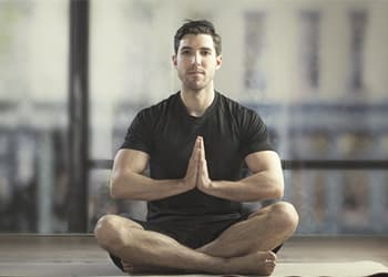 Man doing yoga as a means of self care