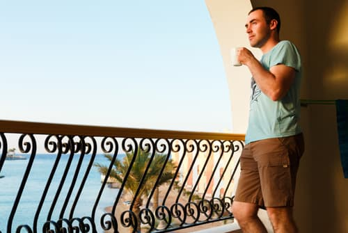 Man standing on balcony overlooking ocean portraying addict at luxury rehab facility