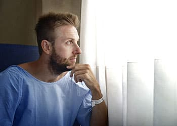 Male patient next to hospital window