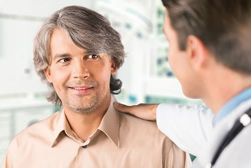 doctor reassuring patient with a hand on the shoulder