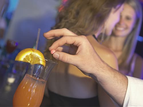 Man drugging woman's drink