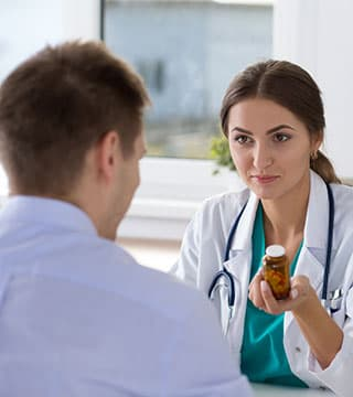 Doctor handing prescription bottle to patient
