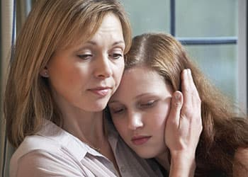 mother comforting addict daughter