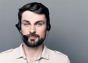 man with phone call headset looks into camera