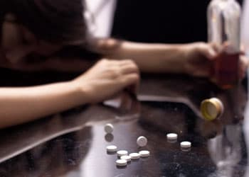 Alcohol and pills on table
