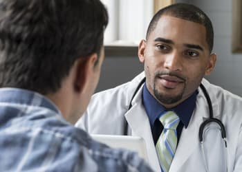 Man portraying doctor speaking with patient about medical detox