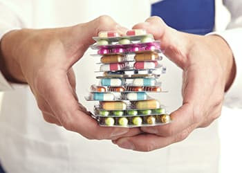 Man holding a stack of various pills