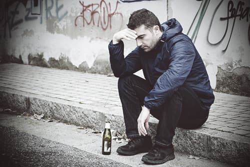 man drinking alcohol depressed sitting on the curb