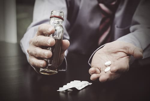 man holding alcohol bottle and pills
