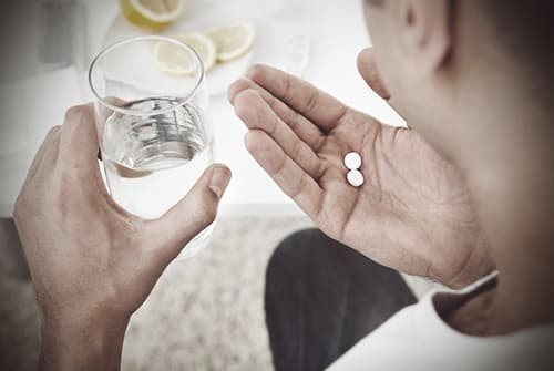 drugabuse-shutterstock183268427-man_holding_white_pills-feature_image