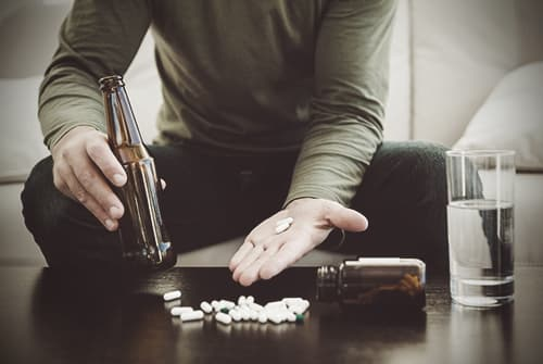 man mixing alcohol with pills