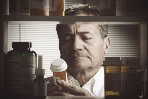 man looking at prescription bottle