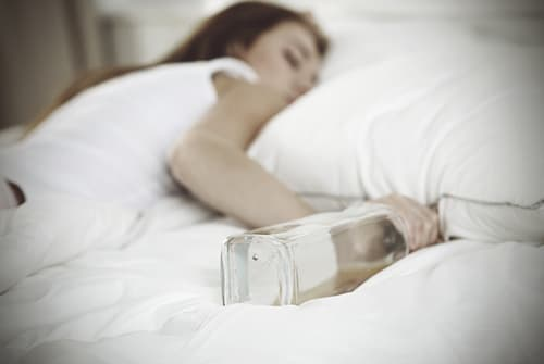 woman passed out on bed with alcohol bottle