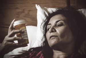 drugabuse_istock-22554925-lady-in-bed-reading-pill-bottle