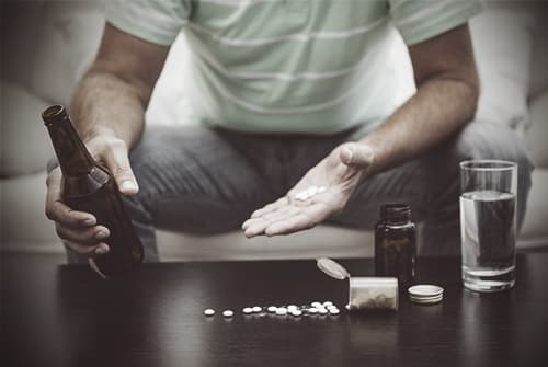 Man with pills on table and alcohol