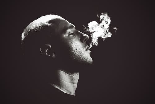 guy blowing smoke with a black background