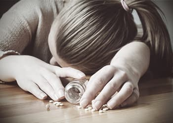 narcotic-overdose-woman-on-ground-with-spilt-pills