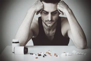 drugabuse_shutterstock-182622683-guy-staring-at-pills-on-table