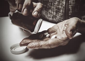 old-man-hands-pouring-pills-into-hand-addicted-to-pain-killers