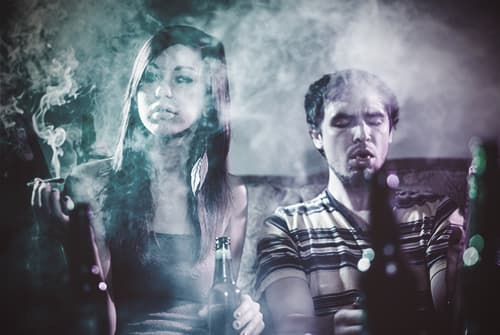 drugabuse_shutterstock-219594313-smoking-at-a-party-guy-and-girl-on-couch-in-cloud-of-smoke