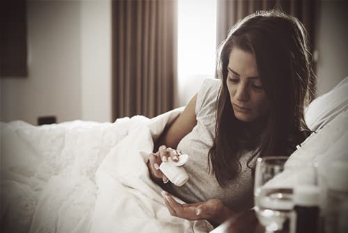 drugabuse_shutterstock-310310438-women-in-bed-pill-FI