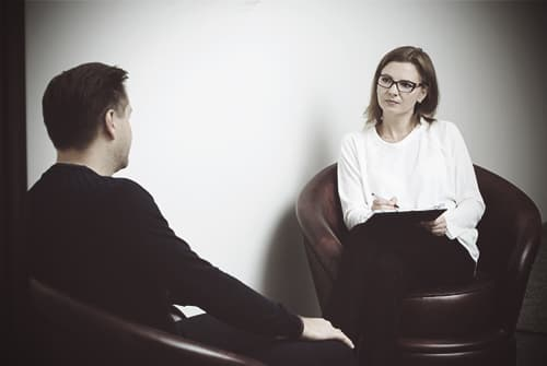 man-in-counselling-session-explaining-addiction-to-woman-therapist