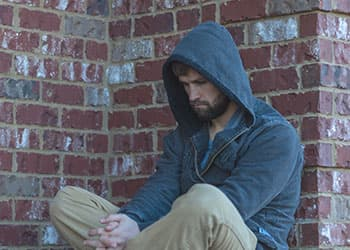 man who has been treated with vivitrol contemplating while sitting up against brick wall