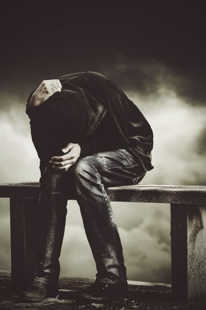 Depressed man holding his head