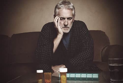 Man looking at pills depressed