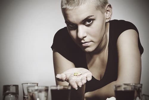 Woman displaying pills with alcohol