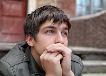 teen boy sitting on steps thinking about lean addiction
